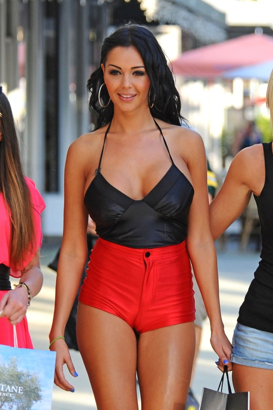 French model and reality TV star Nabilla Benattia leaves little to the imagination in a loose black tank top and high-waisted shorts while filming in Miami